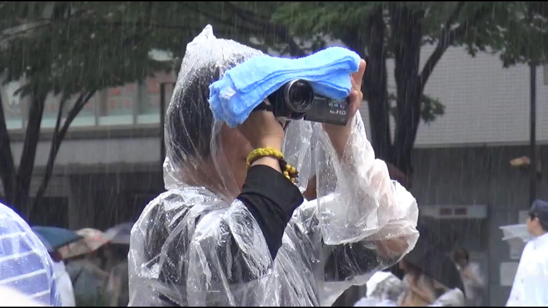 Frau filmt im Regen und benutzt die gleiche Kamera wie ich